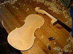 A violin back and a neck on the workbench